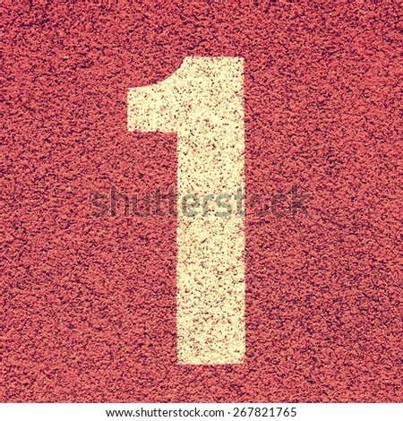 Number one. White track number on red rubber racetrack, texture of running racetracks in small stadium - stock photo