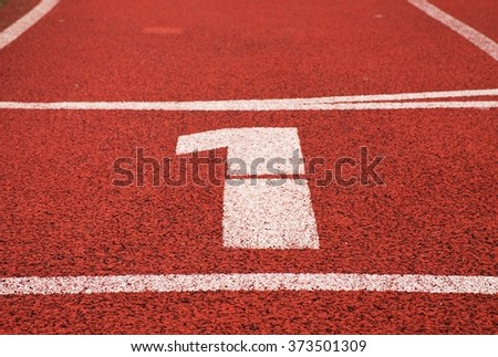 Number one. White track number on red rubber racetrack, texture of running racetracks in small stadium