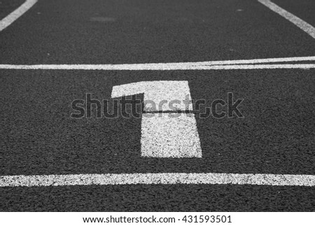 Number one. White track number on red rubber racetrack, texture of running racetracks in small stadium.  Black and white photo - stock photo