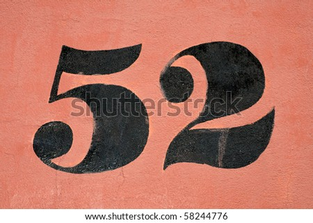 number 52 painted in black on a red wall - stock photo