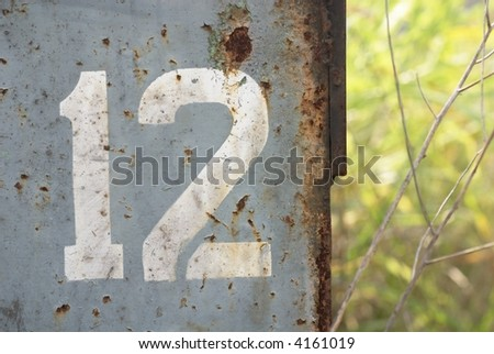 number 12 painted on rusted metal - stock photo