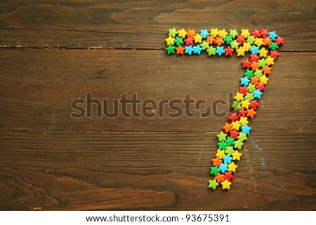 Number seven made with star shape candies on a wooden table - stock photo