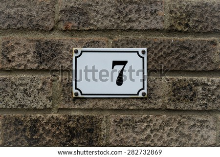 Number 7 seven plated on brick wall  conceptual image details - stock photo