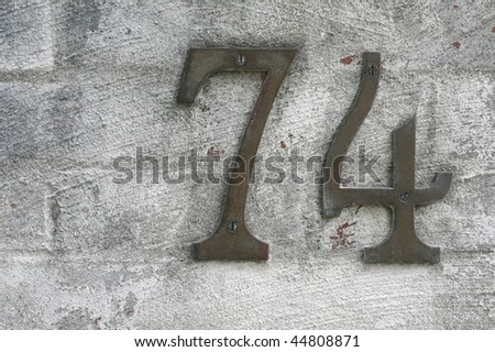 number seventy four for home address against textured brick wall - stock photo