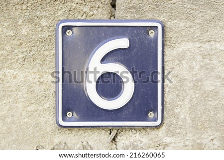 Number six on a wall of a house, detail of a number of information, even number - stock photo
