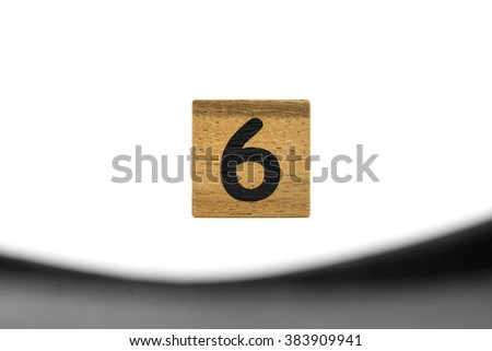 number six on wood and black foreground and white background