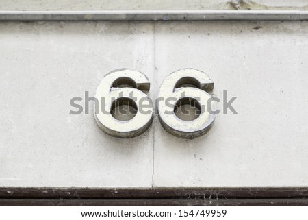 Number sixty-six on the wall, detail of a wall with a number of information - stock photo