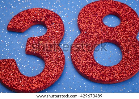 Number thirtyeight red color over a blue background. Anniversary