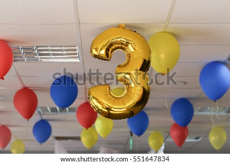 Number three golden balloon photo on the ceiling with other colourful balloons