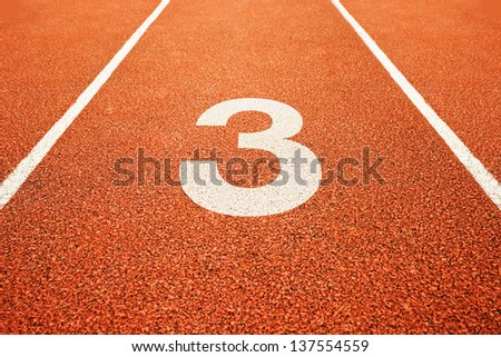 Number three on athletics all weather running track - stock photo