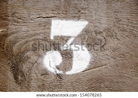 Number three painted on wood, detail of a white number painted on a wall, indication and information - stock photo