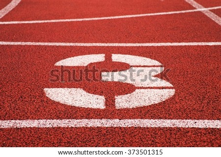 Number three. White track number on red rubber racetrack, texture of racetracks in outdoor stadium - stock photo