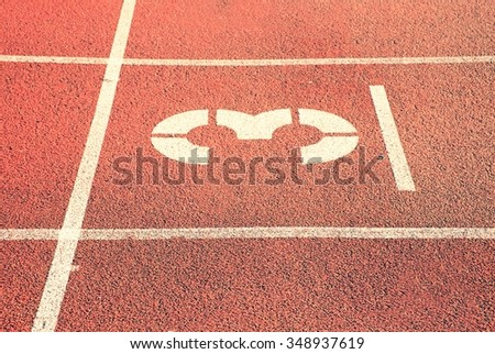 Number three. White track number on red rubber racetrack, texture of racetracks in stadium - stock photo
