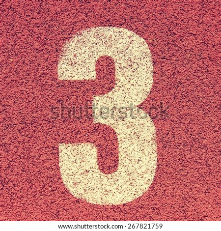 Number tree. White track number on red rubber racetrack, texture of running racetracks in small stadium - stock photo