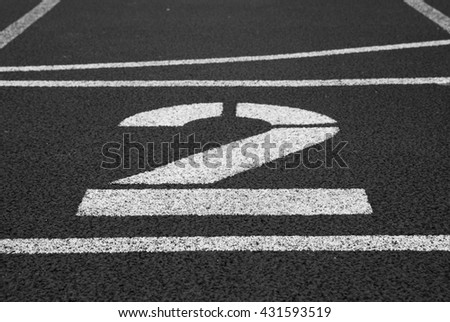 Number two. Big white track number on red rubber racetrack. Gentle textured racetracks in small outdoor stadium.  Black and white photo
