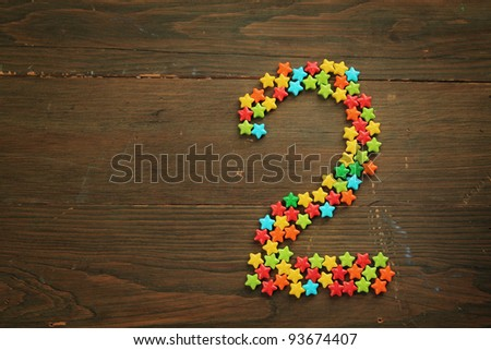 Number two made with star shape candies on a wooden table - stock photo