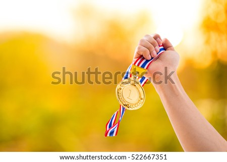 Number 1 winner holding medal gold award to sky.