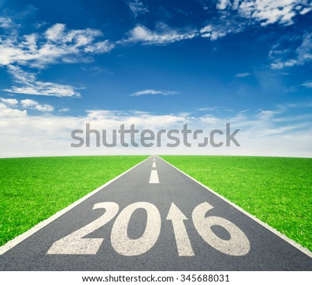 Number 2016 written on road in grass field against cloudy blue sky - stock photo