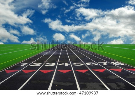Numbered lanes on a mile running fitness athletic black track. - stock photo