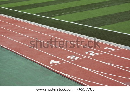 numbered running track with green field - stock photo