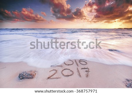 Numbers 2017 and 2016 handwritten on seashore sand during sunset hour . Concept of upcoming new year and passing of time.