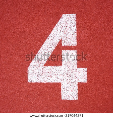 Numbers four on red running track - stock photo
