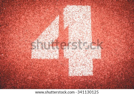 Numbers four on rubber running track standard red color. - stock photo