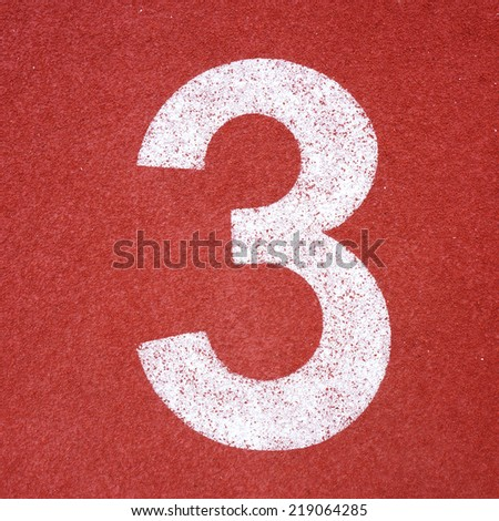 Numbers three on red running track - stock photo