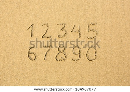 Numbers written on a sandy beach. - stock photo
