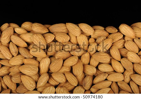 Numerous almonds arranged in a pie for a product photograph. Almonds are considered healthy and good for the heart.