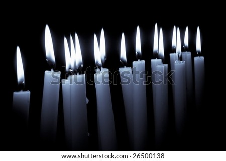 Numerous lighted table candles against a black background