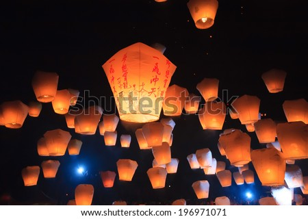 Numerous orange lanterns illuminate a dark starry sky.