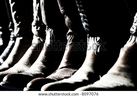 Numerous pairs of Cowboy Boots lined up in high-contrast sun and shadow - can represent western, rodeo, cowboy, etc. (shallow focus point on middle of image). - stock photo