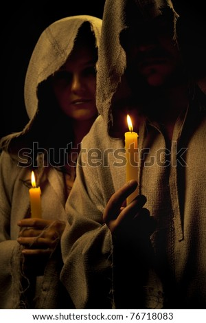 Nun and monk  praying with candles in their hands - stock photo