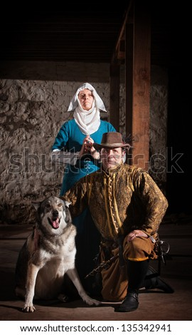 Nun behind kneeling swashbuckler and dog in medieval character - stock photo