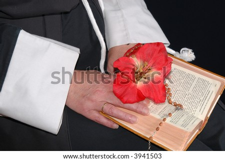 Nun hands resting on the book of faith, the bible, rosary and flower in hand.  Religion, christianity, lifestyle concept - stock photo