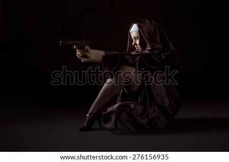 Nun shooting from gun sitting on her knees. Low key photo on black background. - stock photo