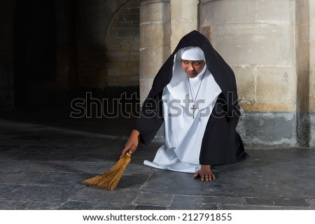 Nun sweeping the floor of a medieval abbey with a hand brush - stock photo