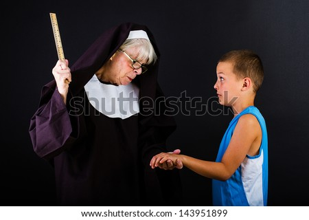 Nun threatening a young boy with a ruler. - stock photo