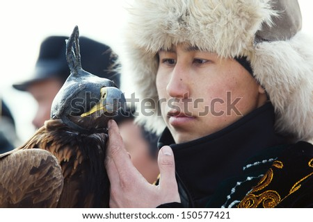 NURA, KAZAKHSTAN - FEBRUARY 23:  An eagle sits on an unidentified man's hand in Nura near Almaty on February 23, 2013 in Nura, Kazakhstan. The traditional event happens yearly and the place becomes as a medieval times city.