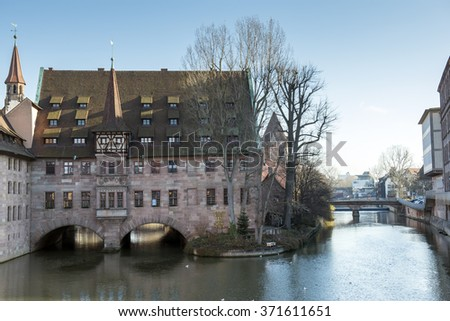 Nuremberg, Germany -Dec. 20, 2015: Heilig-Geist-Spital (Hospice of the Holy Spirit) at night in Old Town Nuremberg, Germany. - stock photo
