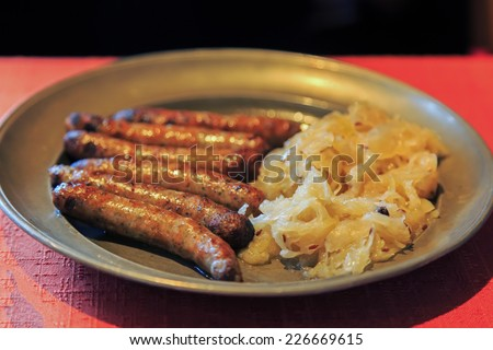 Nuremberg sausages with cabbage and spices on metal plate  - stock photo