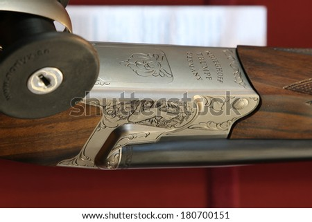 NURNBERG, GERMANY - MARCH 9:  Handmade engravings on Krieghoff Trumps hunting shotgun on display at IWA 2014 & Outdoor Classics exhibition on March 9, 2014 in Nurnberg, Germany - stock photo