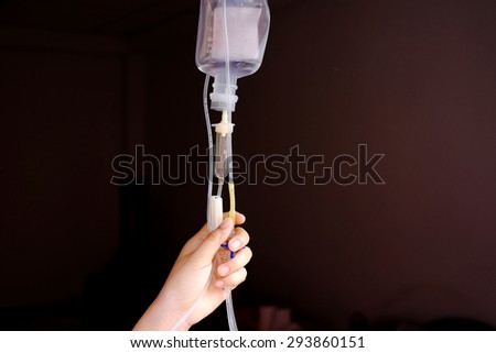 Nurse adjusting infusion bottle in hospital - stock photo
