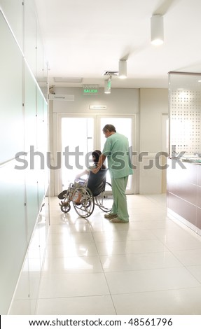 Nurse and a patient using a wheelchair at a hospital hall - stock photo