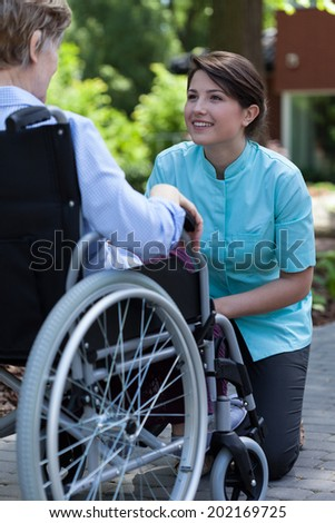 Nurse and disabled woman resting in a garden - stock photo