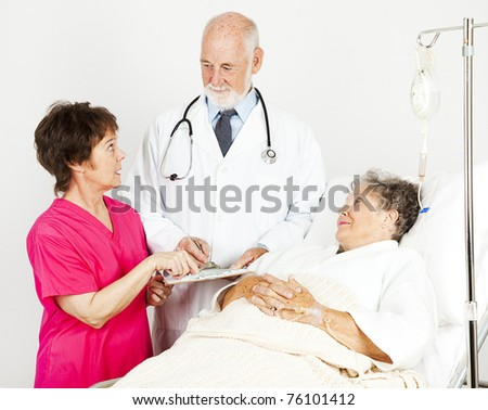 Nurse and doctor discussing a hospital patient's chart. - stock photo