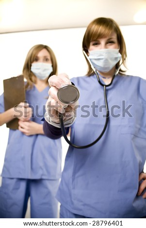 nurse and doctor in hospital ready to listen with stethescope - stock photo