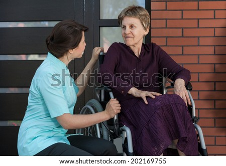 Nurse and elderly lady in front of house - stock photo