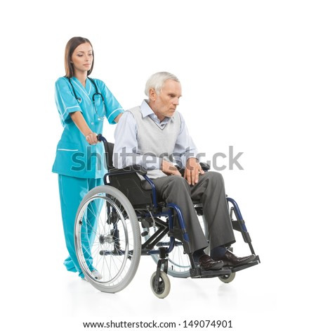 Nurse and patient. Confident young nurse walking with patient sitting on the wheelchair while isolated on white